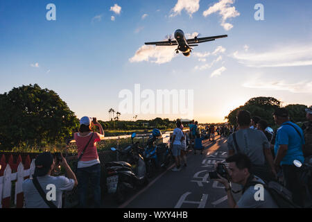 Spectators watch and take photos from 'Airplane Alley' as an aircraft flies low over their heads on approach to Songshan Airport, Taipei - Stock Photo