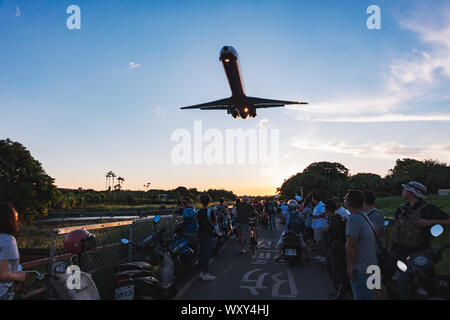 Spectators pose for photos while a McDonnell Douglas MD-82 screams over their heads on approach to Songshan Airport, Taipei - Stock Photo