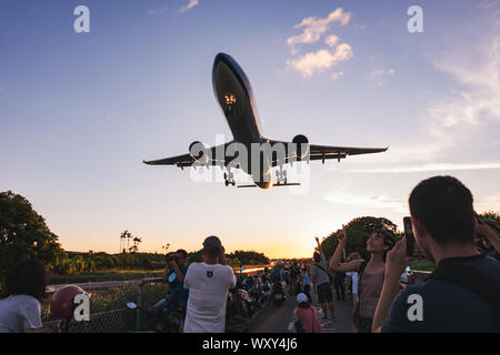 Spectators point and pose for photos as an Airbus A330-300 flies very low over their heads on approach to Songshan Airport, Taipei - Stock Photo