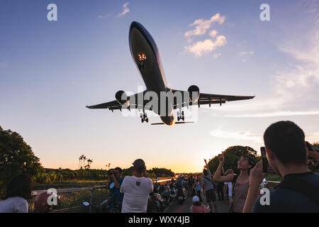 Spectators pose for photos as an Airbus A330-300 flies very low over their heads on approach to Songshan Airport, Taipei