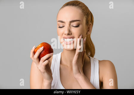 Tooth problems. Young woman having toothache, biting apple - Stock Photo
