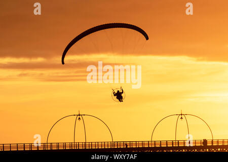 Southport. Merseyside. UK Weather. 18th Sept, 2019. UK Weather; Sunny colourful end to the day as powered hand glider silhouetted in the evening sun, takes a powered flight in light winds as the sun sets in Southport. Paramotor flying machines & Stunt flying as the sun sets; a hand glider silhouette against orange clouds, enjoying flying over the Irish Sea coast. Credit:MWI/AlamyLiveNews. - Stock Photo