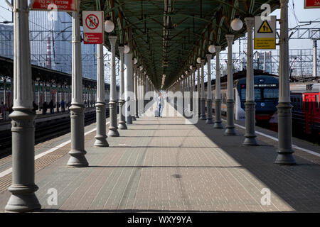 People walk on the platform of the Moscow Belorussky railway station with commuter trains and long-distance trains in Moscow, Russia