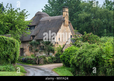 Thatched cottage in the village of Stanton, Cotswolds district of Gloucestershire.  It's built with a honey-coloured Jurassic limestone - Stock Photo