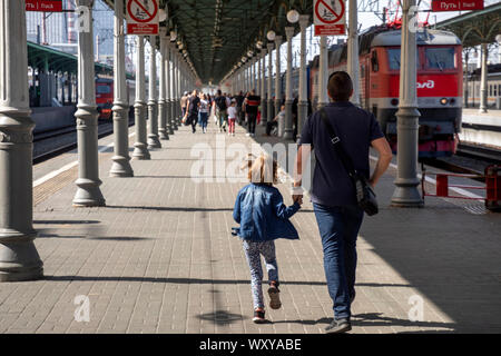 People walk on the platform of the Moscow Belorussky railway station with commuter trains and long-distance trains in Moscow, Russia - Stock Photo