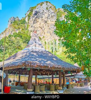 AO NANG, THAILAND - APRIL 25, 2019: The shady hut of the beach bar, located among the tropical greenery at the huge rock, on April 25 in Ao Nang - Stock Photo