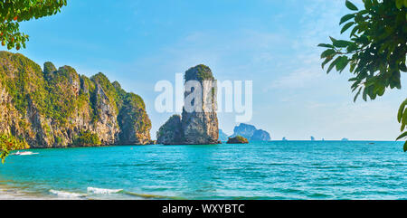Enjoy the tall rocky cliffs of Ao Nang coastline, washed by Andaman sea, Krabi, Thailand - Stock Photo