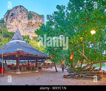 AO NANG, THAILAND - APRIL 25, 2019: The sandy alley through the  evening beach with a view on spread trees and cafe-bar in wooden hut, on April 25 in - Stock Photo