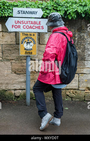 Unindentified woman looking at signs with directions in the Cotswold village of Stanway, Gloucestershire, Cotswolds, UK - Stock Photo