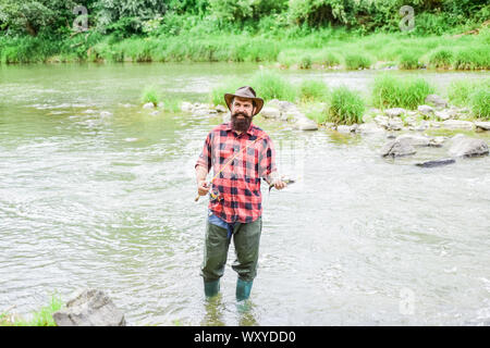 Fish on hook. Brutal man stand in river water. Man bearded fisher. Fisher masculine hobby. Fishing requires to be mindful and fully present in moment. Fisher fishing equipment. Rest and recreation. - Stock Photo
