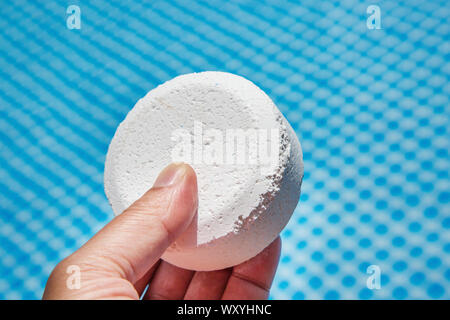 Hand holding Chlorine Pellets with inflatable pool on background - Stock Photo