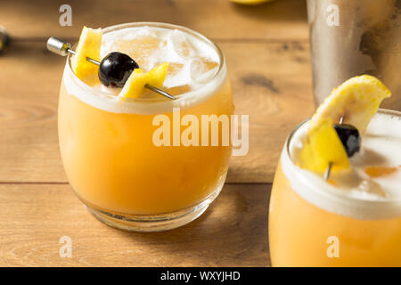 Sweet Homemade Whiskey Amarreto Sour Cocktail with a Cherry - Stock Photo