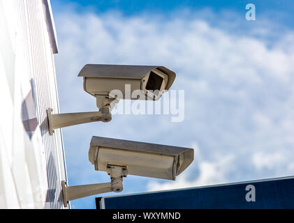 closeup on two security CCTV cameras or surveillance system in office building - Stock Photo