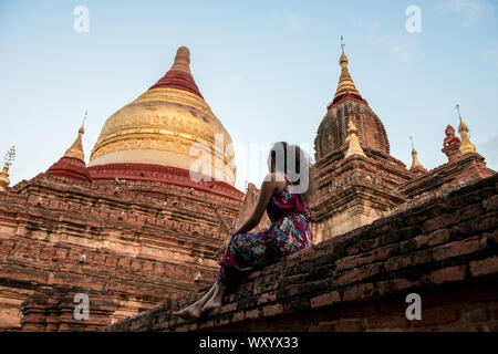 Wide angle picture of brunette woman looking the architectonic Dhammayazika Temple, an amazing buddhist pagoda in Bagan in Myanmar - Stock Photo