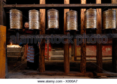 Prayer wheels and a Tibetan pilgrim, an elderly Tibetan woman, in Jokhang Temple, Lhasa, Tibet, China, Asia - Stock Photo