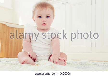 Portrait baby girl sitting on floor - Stock Photo
