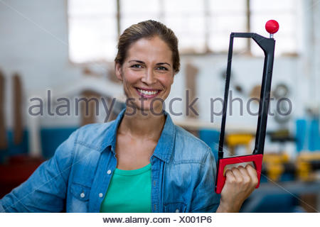 Happy female carpenter holding coping saw - Stock Photo