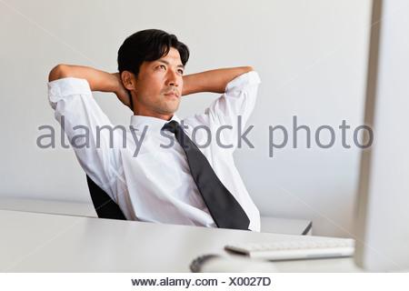 Businessman thinking at his desk - Stock Photo