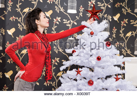 Young woman decorating christmas tree - Stock Photo