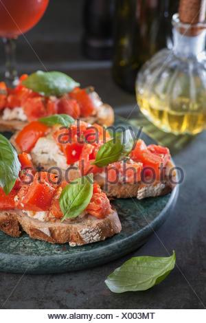 Italian tomato bruschetta with basil and olive oil on crusty slice of bread - Stock Photo