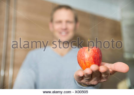 Man offering  red apple - Stock Photo