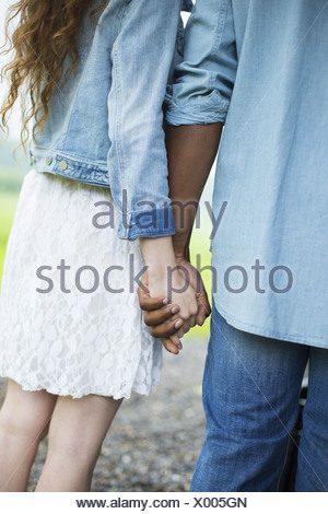 A young man and woman a couple holding hands. Back view. - Stock Photo