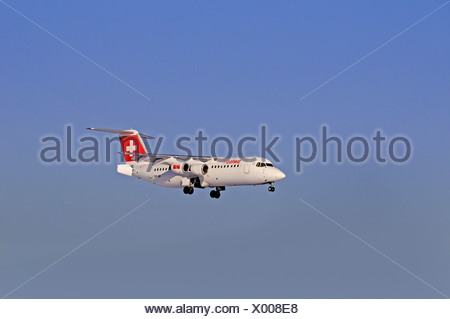 Commercial aircraft, Swissair, AI(R) Avro RJ & BAe 146, approaching to land against a hazy sky - Stock Photo