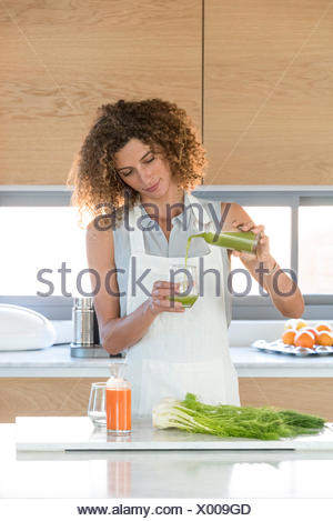 Woman pouring vegetable juice into a glass - Stock Photo