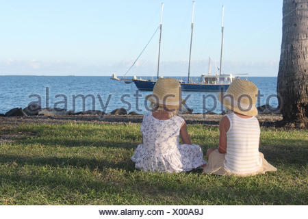 Two girls sitting on grass looking at boat, Port Douglas, Queensland, Australia - Stock Photo