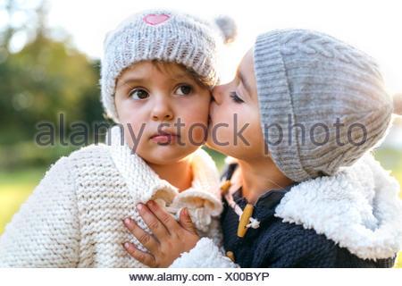 Little girl kissing another little girl - Stock Photo