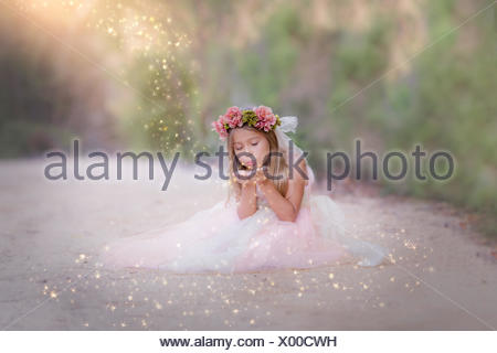Girl sitting in the road, blowing glitter - Stock Photo