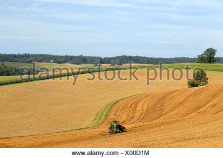tractor with grubber on hilly fieldlandscape in autumn, Germany, Bavaria - Stock Photo