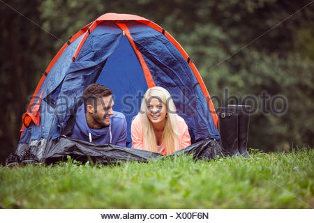 Happy couple lying in their tent - Stock Photo