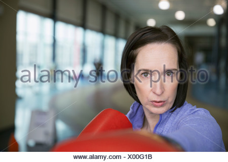 Close up portrait of serious woman boxing - Stock Photo