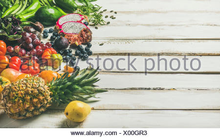 Helathy raw vegan food cooking background. Fresh fruit, vegetables, greens, superfoods over white wooden table, copy space. Clean eating, alkaline die - Stock Photo