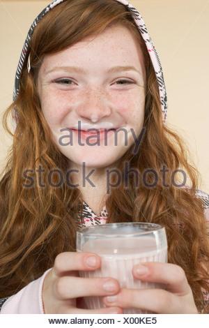 Young girl indoors drinking a strawberry milkshake - Stock Photo