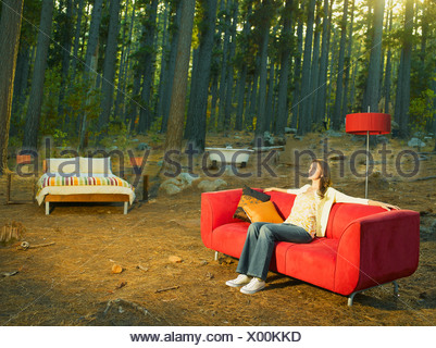 A woman with home furnishings sitting outdoors in the woods - Stock Photo