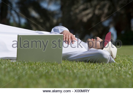 Young man lying on grass - Stock Photo