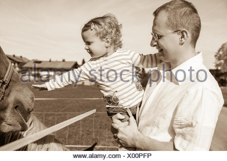 Father, Daughter, horse paddock fence, animal - Stock Photo
