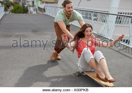 MODEL RELEASED. Young woman sitting on skateboard with man pushing. - Stock Photo