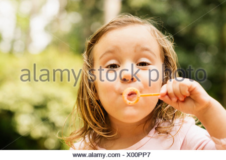 Close up portrait of female toddler blowing bubbles in garden - Stock Photo