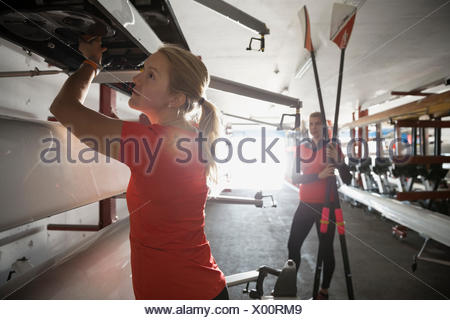 Rower examining scull on rack in boathouse - Stock Photo