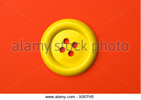 A yellow button on a red background - Stock Photo