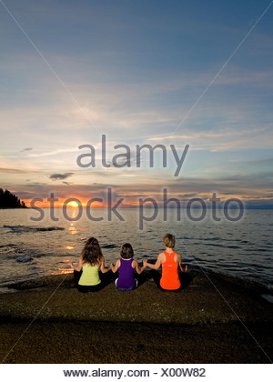 Two women young girl enjoy stunning sunset - Stock Photo