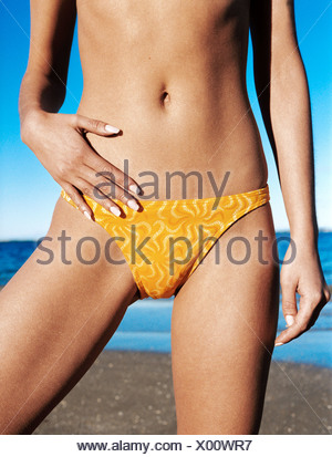 Cropped image of female wearing yellow bikini bottoms one hand on pelvis with thigh turned out, sea in background - Stock Photo
