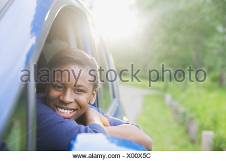 Smiling teenage girl looking out of car window - Stock Photo