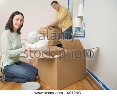 Couple unpacking boxes in new house - Stock Photo