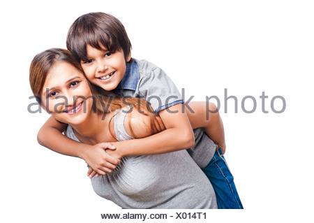 Portrait of a boy riding piggyback on his mother - Stock Photo