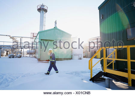 Male worker walking in snow at gas plant - Stock Photo
