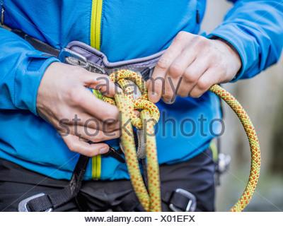 Rock climber tying rope - Stock Photo